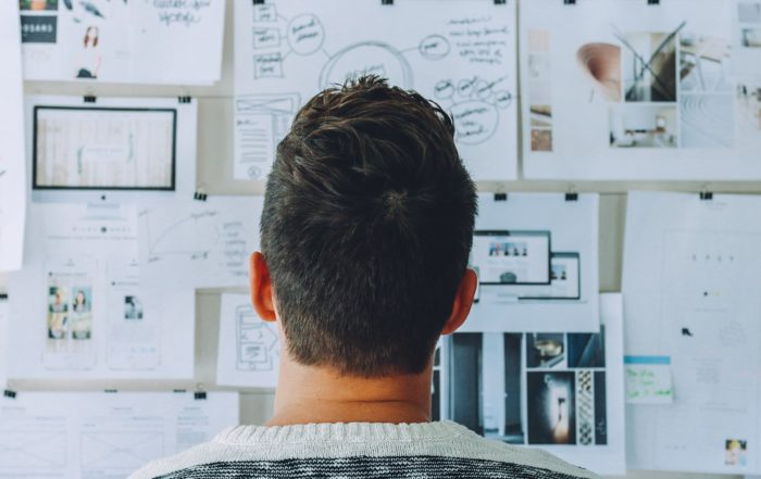 man looking at printouts on a whiteboard