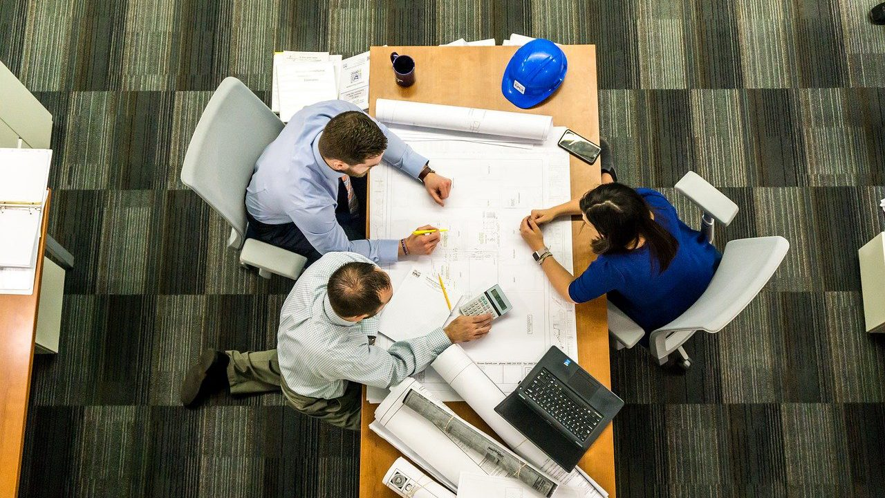 Three office workers sitting around a table with blueprints at a desk.