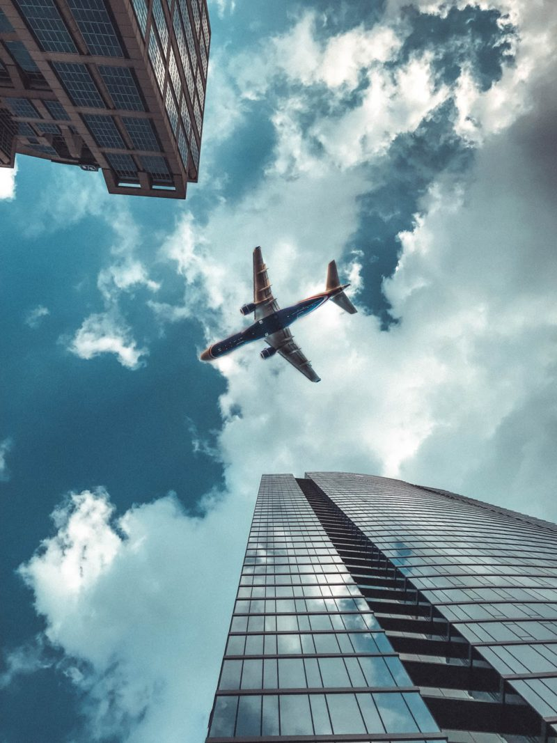 plane flying above buildings