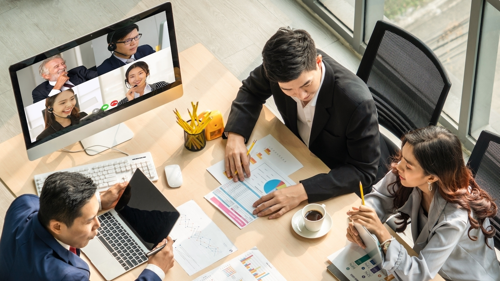 team in office meeting with coworkers on video call