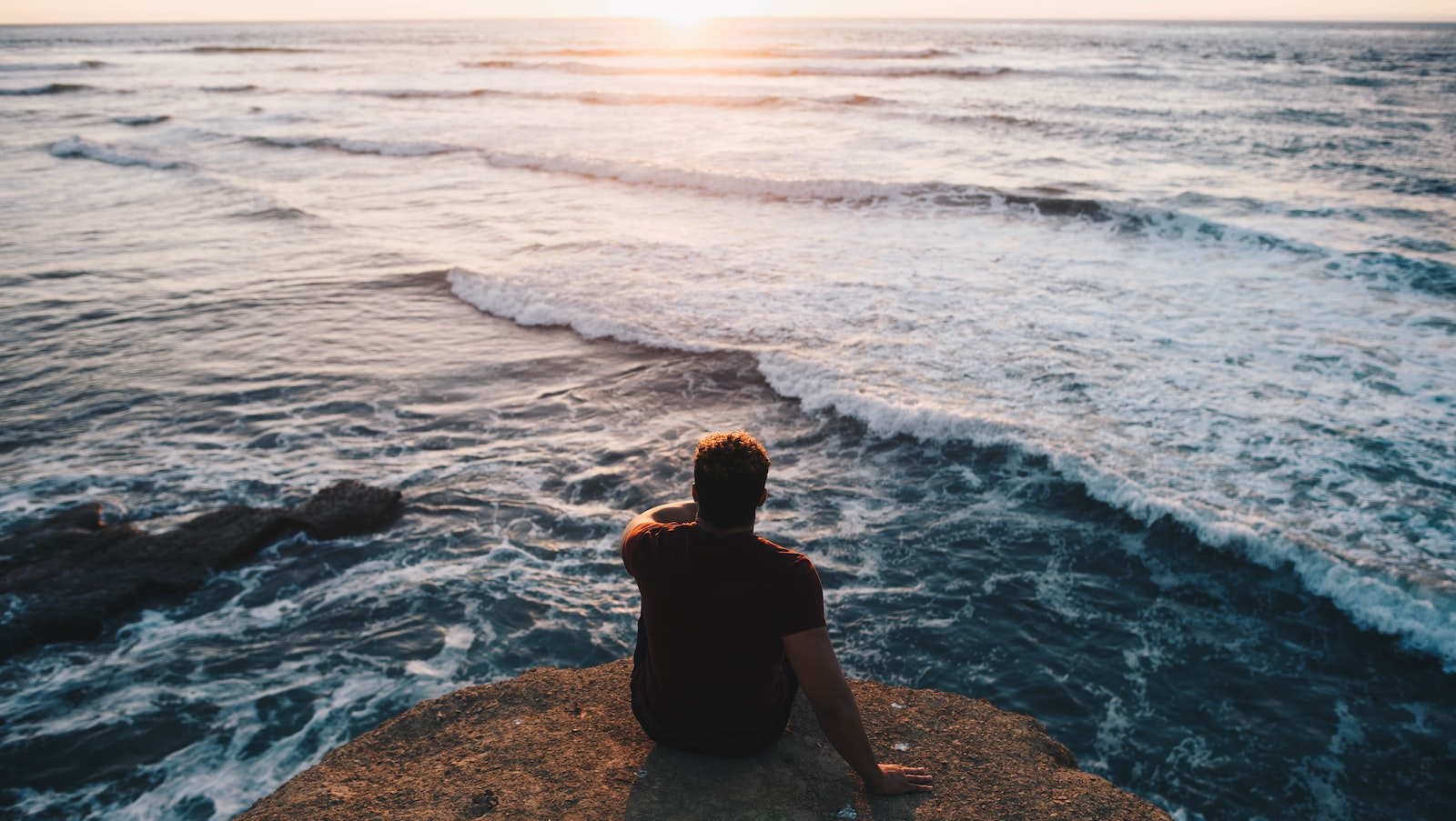 man on cliff overlooking ocean