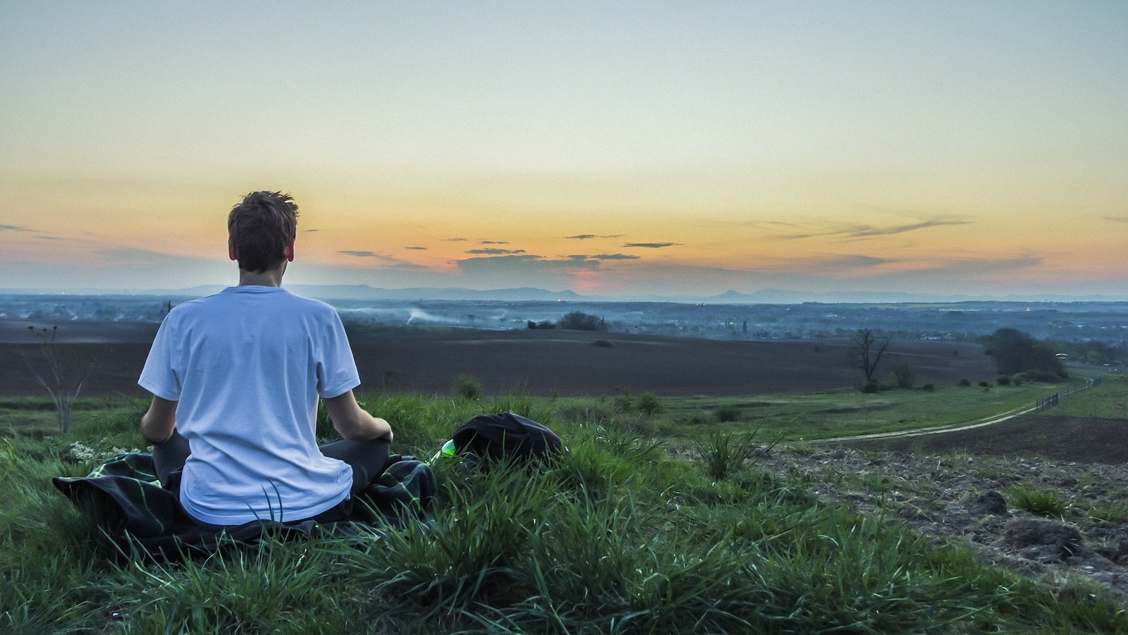 person meditating looking over landscape