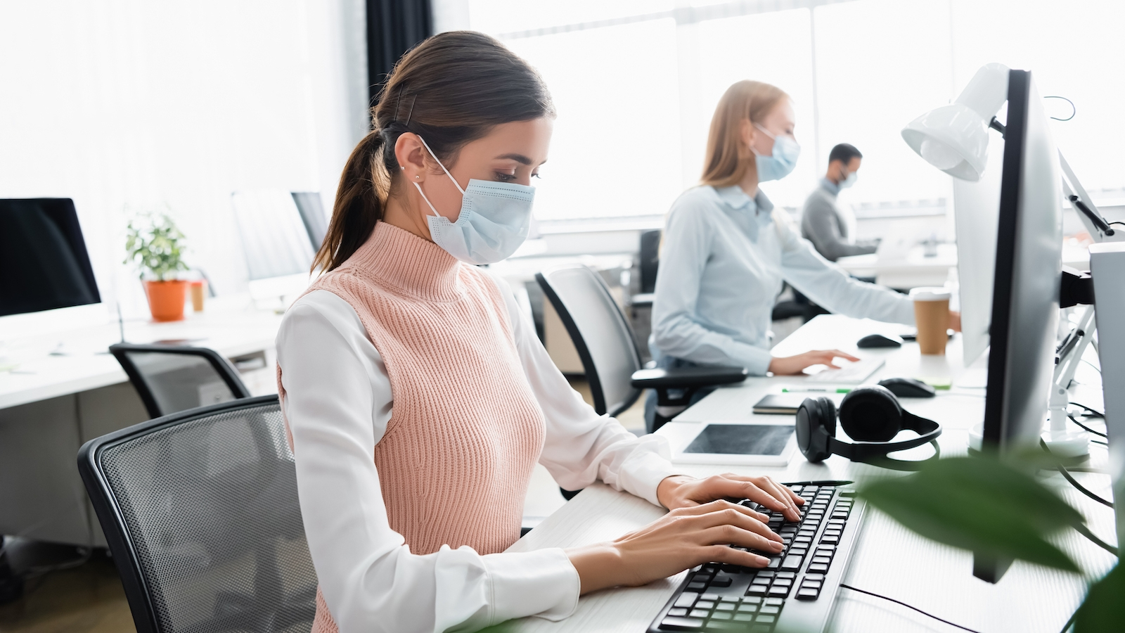 woman at desk with mask